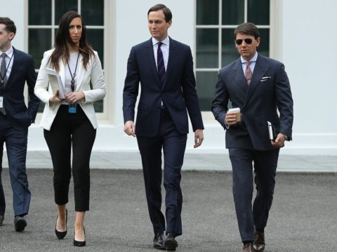 three men and one woman, all white, walk on a driveway with part of a wall of the White House behind them