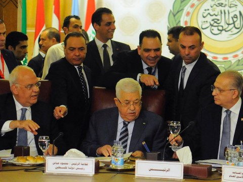 Mahmoud Abbas sits at a table flanked by two other older men. Several other men mill around behind them.
