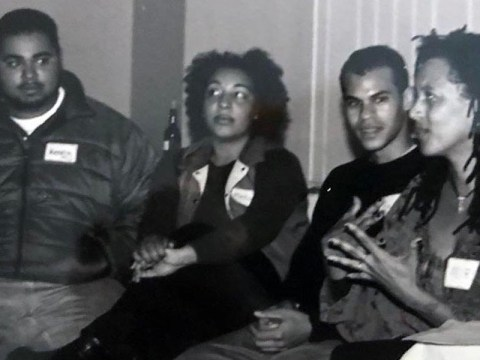 a black and white photo of two black men and two black women sitting and talking