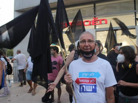 a man in a mask holds up a black flag