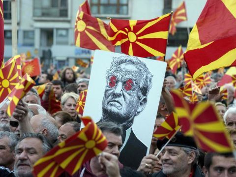 Protesters in Macedonia hold a placard depicting billionaire George Soros with dollar signs for eyes during a demonstration against a deal between the country's Social Democrats and the Albanian Democratic Union for Integration. (Photo/JTA-Robert Atanasovski-AFP-Getty Images)
