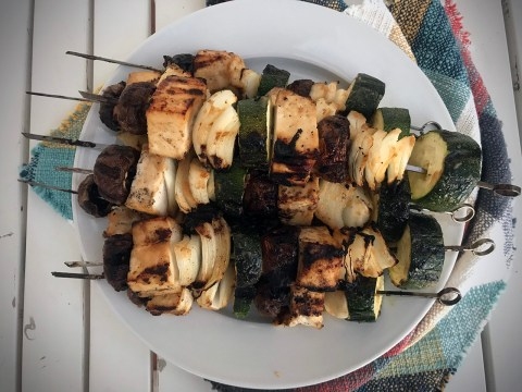 white plate with three skewers of tofu and zucchini chunks