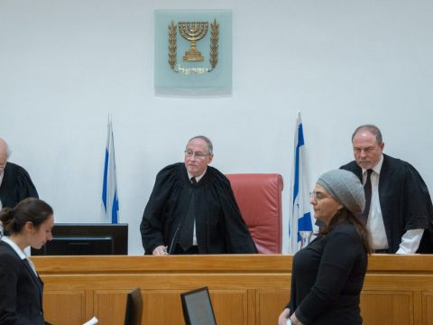 three judges in black robes look on as two women stand