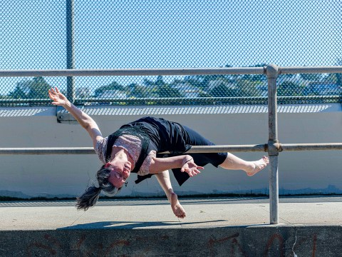 Choreographer Jo Kreiter improvises on a pedestrian bridge. (Photo/Kyle Adler Photography)