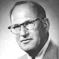 black and white photo of a bald man wearing glasses