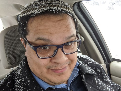 a latino man in a kippah sits in his car, covered in snow