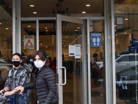 two women wearing face masks, one pushing a stroller, walk out of a store