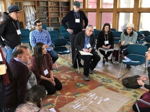 "Mati Esther Engel (bottom right), a performance artist, ritualist and spiritual care practitioner, speaks to participants at a gathering of Kenissa, a network of Jewish ""communities of meaning,"" held in March 2020 in Falls Village, Connecticut. (Photo/JTA-Courtesy Kenissa)"
