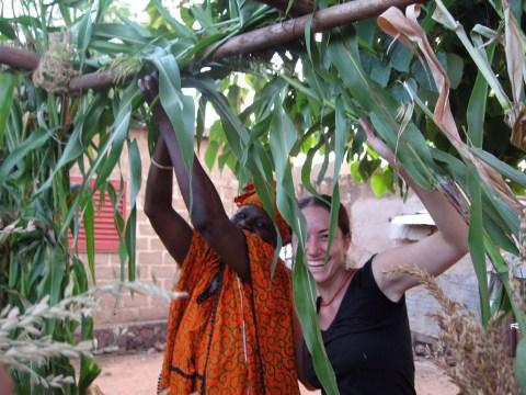 Jessica Beckerman (right) making a sukkah in Mali with Nana Niare.