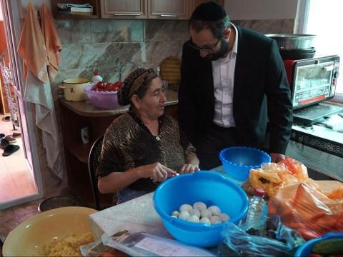 Zoya Avadayev discusses cooking Jewish dishes with Rabbi Tsadok Ashurov in Krasnaiya Sloboda, Azerbaijan, July 21, 2018. (Photo/JTA-Cnaan Liphshiz)