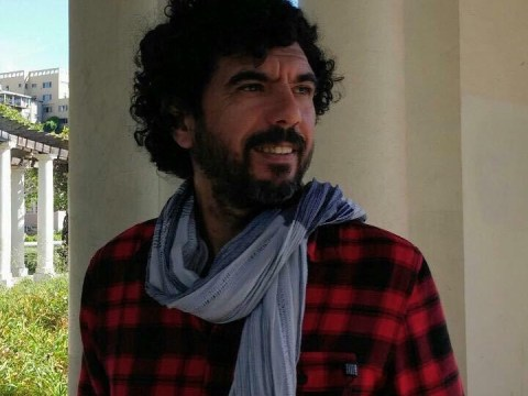 man with dark curly hair, scarf and red plaid shirt stands in front of white columns