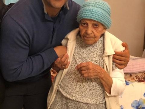 Vysoký mladý muž drží ramena velké dámy v modrém klobouku