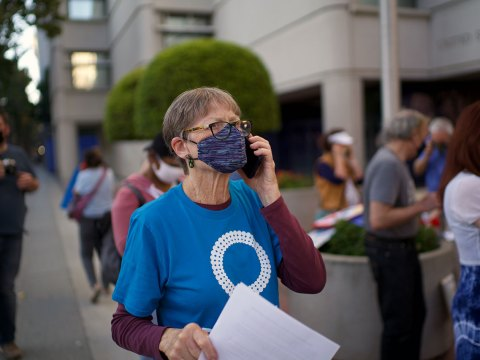 """Michal Strutin of Dayenu Circle of Jewish Silicon Valley calls Senator Feinstein's office to demand she vote for climate action at the """"Make a Holy Noise for Climate Change"""" demonstration on Aug. 25 in San Jose.(Photo/George Barahona)"""