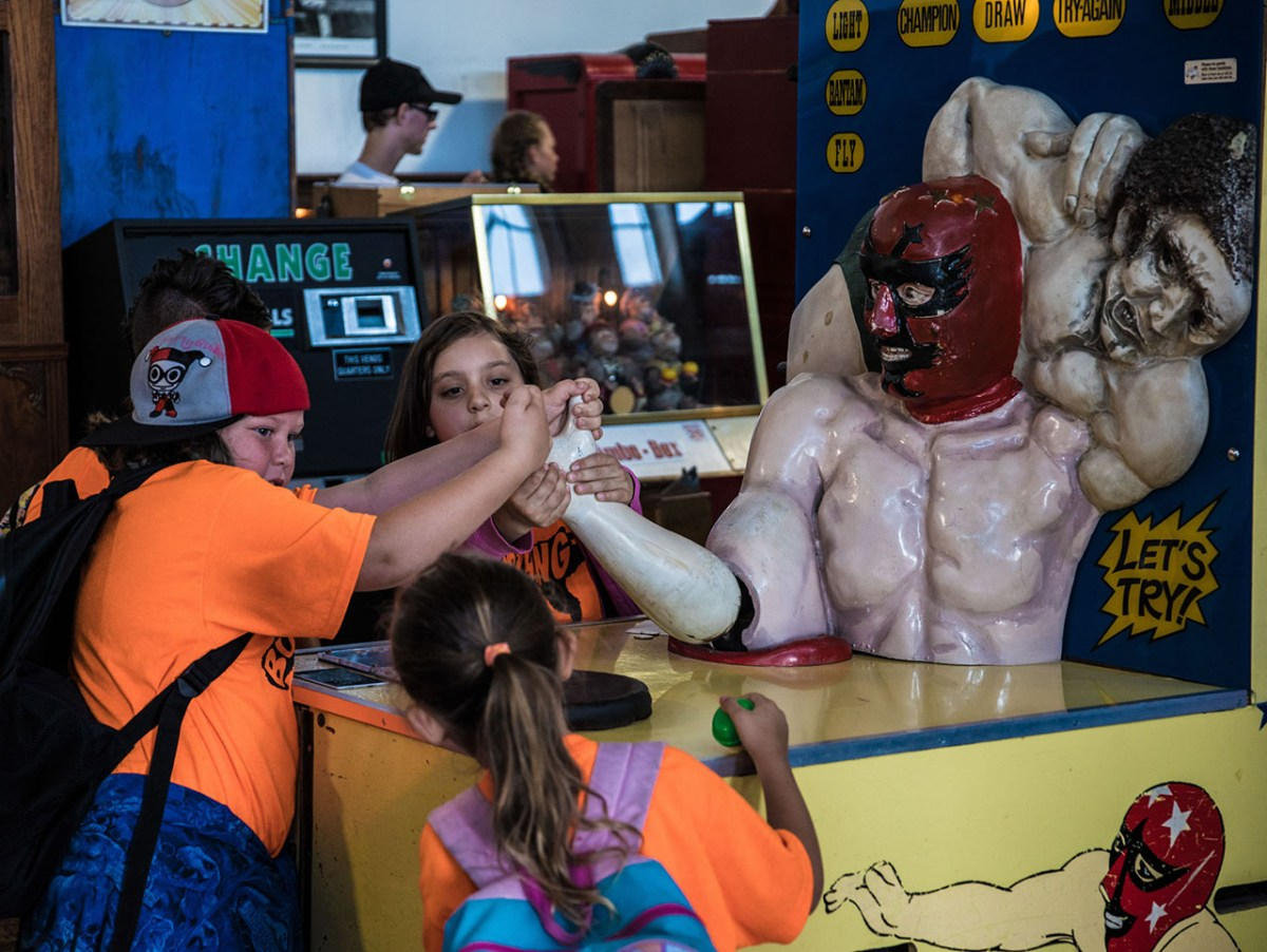 Children play with an arm wrestling game inside the Musée Mécanique. (Photo/Connor Zelinsky)