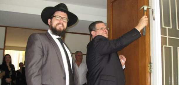 Rabbi Shmueli Feldman stands by as Ambassador Shmuel Ben-Shmuel attaches a mezuzah    Photo: Sylvia Deutsch