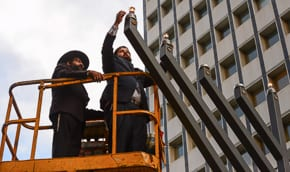 Rabbis Sebban and Rabbi Levy light the Menorah