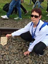 Carol at Auschwitz with a memorial plaque to the Jews of Greece