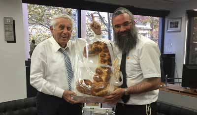 Harry Triguboff raises his finger to show number 1 with his challah and Rabbi Dovid Slavin
