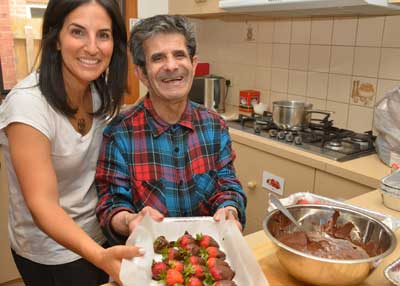 Resident Shabtai Zicband (right) enjoys making chocolate covered strawberries with Galit Ben David.