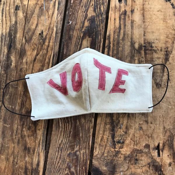 Vote written across a face mask.
