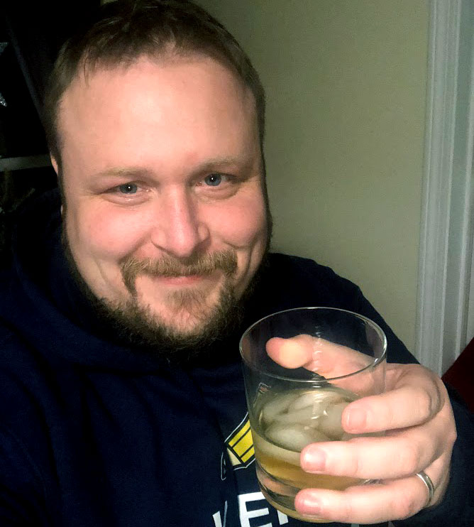 Image of Zack holding a glass of scotch