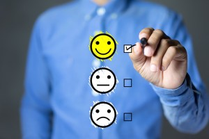 Man in blue shirt rating satisfaction with smiling emoticon