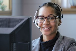 Customer service agent with glasses and headset behind computer