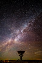 The Milky Way spreads over a satellite dish at the Very Large Array.