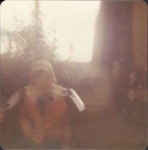 A very blurry photo of a child(?) and a tree(?) indoors