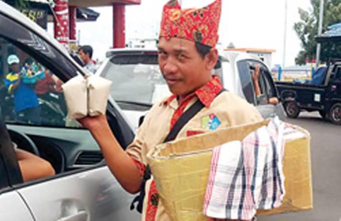 Pedagang-asongan-Ketapang-menggunakan-udheng-khas-Banyuwangi-dan-baju-batik-saat-jualan-pada-Jumat-dan-Sabtu.