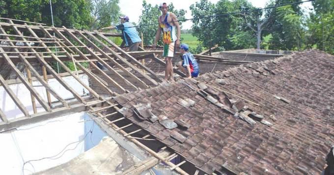 Warga-membersihkan-rumah-milik-Asih-yang-ambruk-di-Dusun-Bolot,-Desa-Aliyan,-Kecamatan-Rogojampi,-Banyuwangi,-kemarin