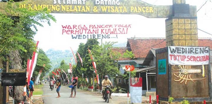 Warga-memasang-spanduk-terkait-pengelolaan-Pantai-Wedi-Ireng,-Dusun-Pancer,-Desa-Sumberagung,-Kecamatan-Pesanggaran,-Banyuwangi,-kemarin