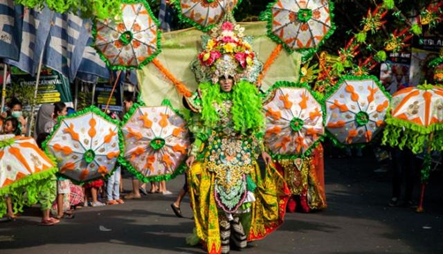 seorang-model-mengenakan-busana-yang-di-penuhi-aksesoris-payung-saat-banyuwangi-ethno-carnival-bec-2014