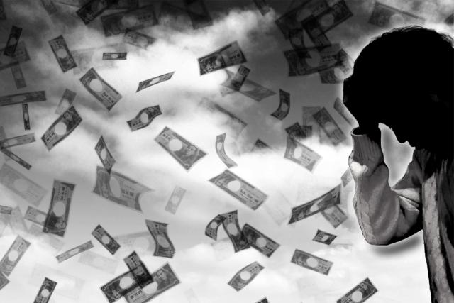 お金が散って、頭を抱える写真