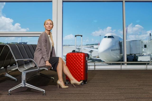 空港のベンチに座るビジネスウーマン