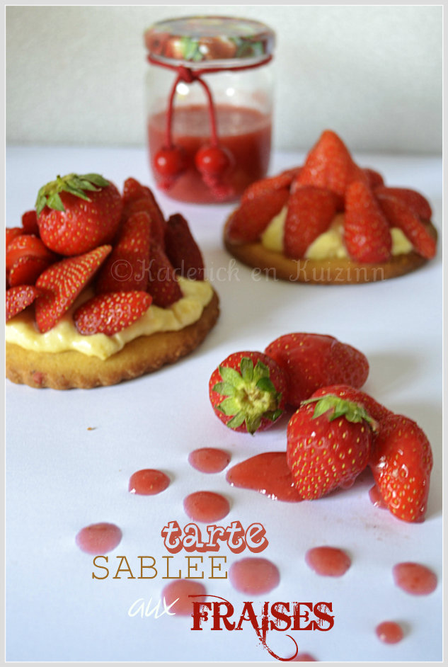 Tarte sablée aux fraises présentées avec des fraises entières et un pot de coulis de fraises