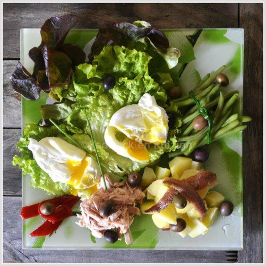 Présentation salade aux oeufs mollets, pomme de terre, haricots verts, thon, poivrons et olives pour une salade complète