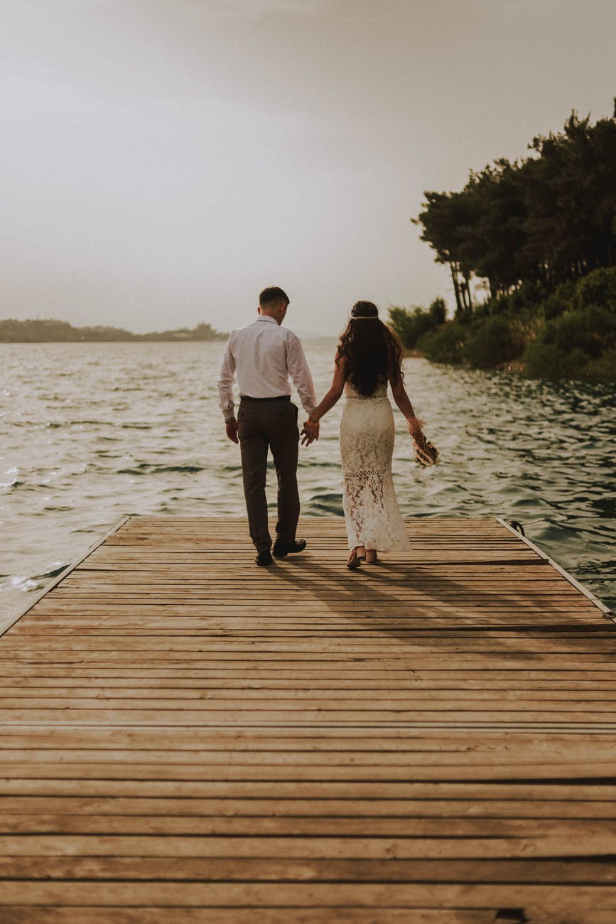 photo of couple standing on wooden planks