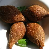 Cooked beef Kebbé or beignets with pignoli nuts and other things inside.