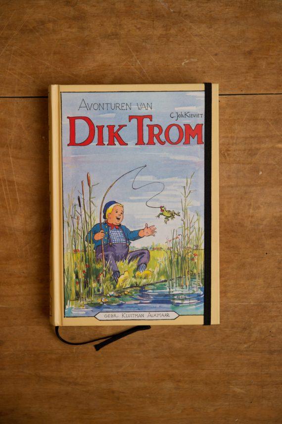 """Van het kinderboek """" Avonturen van Dik Trom _ 54e druk"""" hebben we een notitieboekje gemaakt. Blanco pagina's, voorzien van een zwart elastiek en een lintje."""