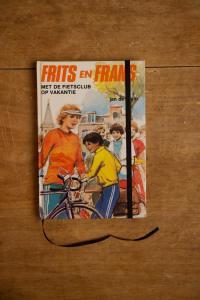 Van het leesboek Frits en Frans met de fietsclub op vakantie is een notitieboek gemaakt. Blanco pagina's, voorzien van een zwart elastiek en een lintje.
