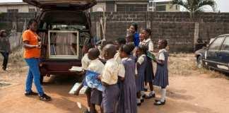 Funmi Ilori (g), devant sa camionnette d'I-Read, explique à des élèves de l'école primaire Bethel l'importance de lire, le 30 janvier 2018 à Lagos, au Nigeria