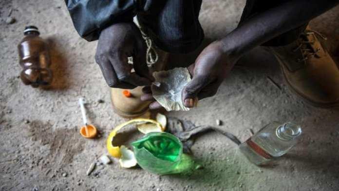 Sur cette photo prise le 17 juillet 2015, un dépendant du cocktail de drogue connu localement sous le nom de Nyaope (Nyope) se prépare à s'injecter de la drogue dans un bâtiment abandonné du township de Simuneye à la périphérie de Johannesburg. © AFP PHOTO/MUJAHID SAFODIEN