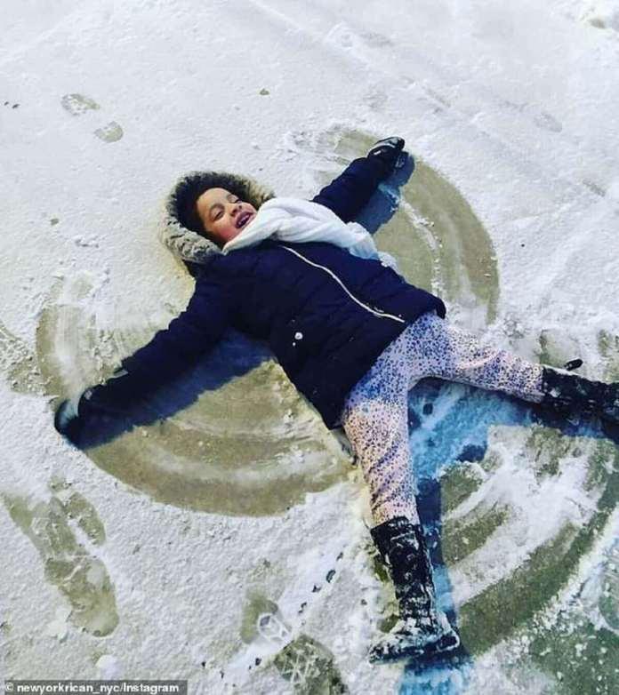 Un enfant est vu en train de fabriquer des anges de neige sur le sol à Chicago, où la neige a déjà commencé à tomber. On s'attend à ce que jusqu'à 12 pouces s'accumulent dans la ville