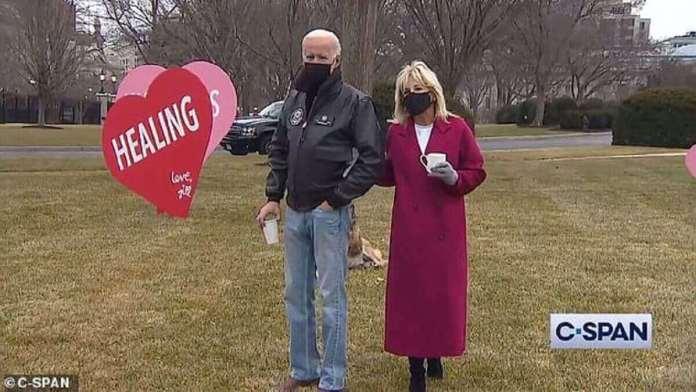 La femme de 69 ans s'est penchée avec le dossier de presse aux côtés de son mari et de leur chien de sauvetage alors qu'elle posait devant les panneaux