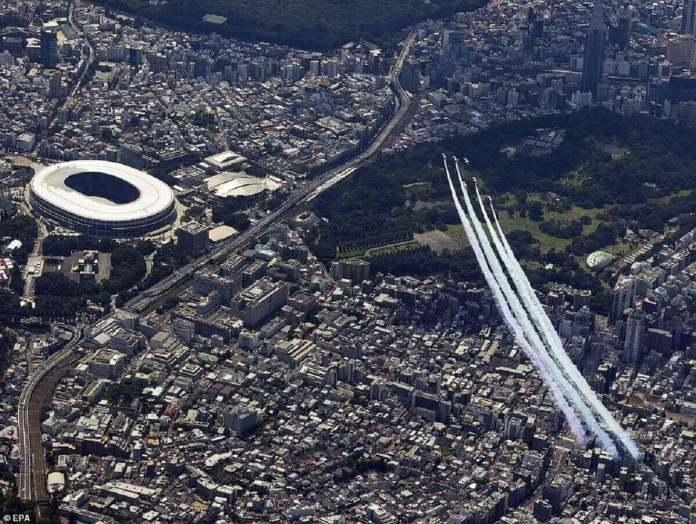 L'équipe de démonstration japonaise Blue Impulse participe à un spectacle aérien au-dessus du stade olympique de Tokyo avant la cérémonie d'ouverture