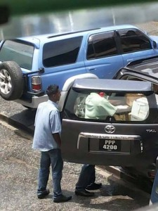 Persons packing items and boxes into the SUV.