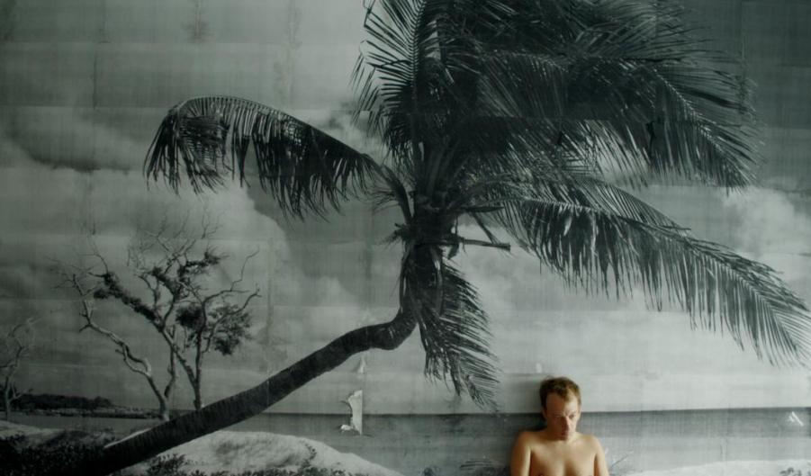 Film Puppe, icke und der Dicke. Mann sitzt vor einer Wand unter einer Palme