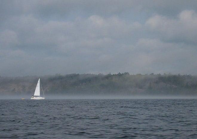 Dimman lägger sig, och segelbåten syns snart inte längre
