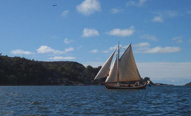 Vacker gammal båt, möter modern farkost i skyn